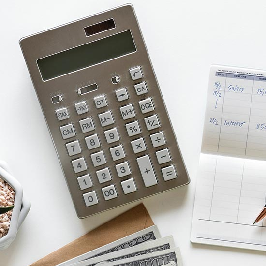 photo of a calculator, checkbook, and monetary bills