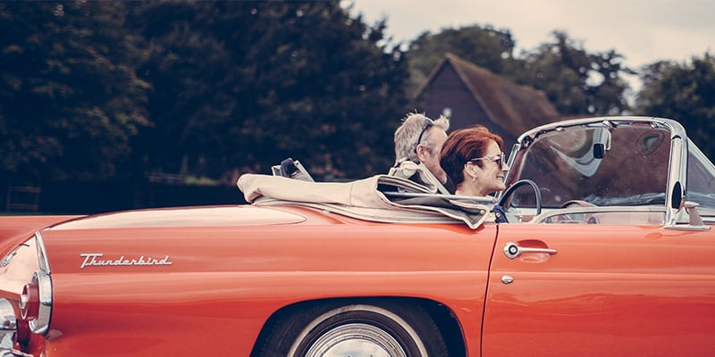 retired couple cruising in their convertible