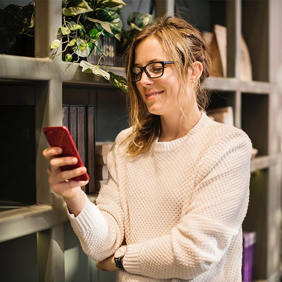 happy woman checking bills on mobile phone