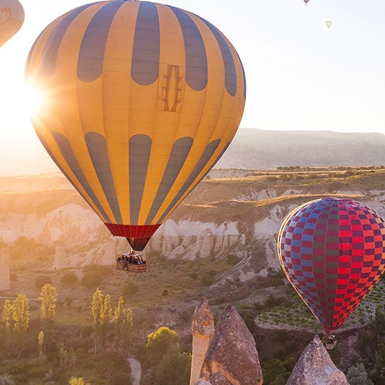 hot air balloons floating above the valley at sunrise