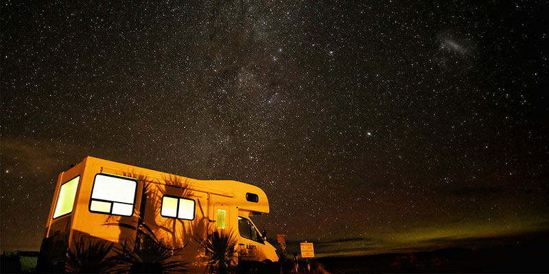 rv outdoors at night beneath the stars of the milky way