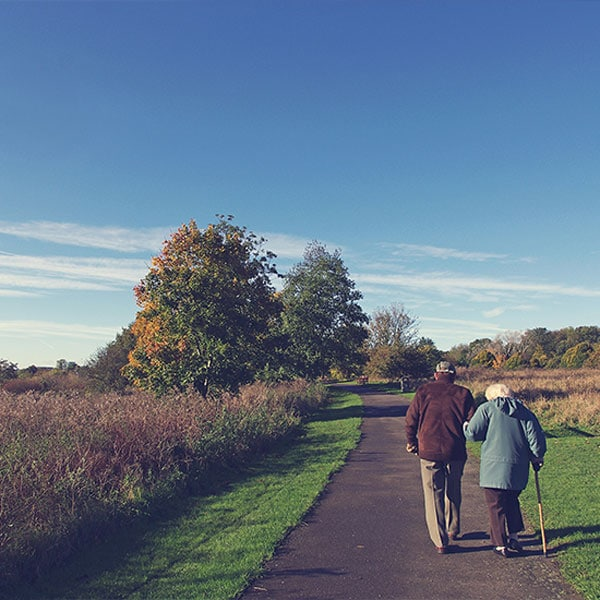 elderly couple walking down a path together