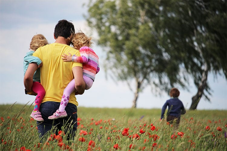 father carrying two daughters as he walks after his son through field of flowers