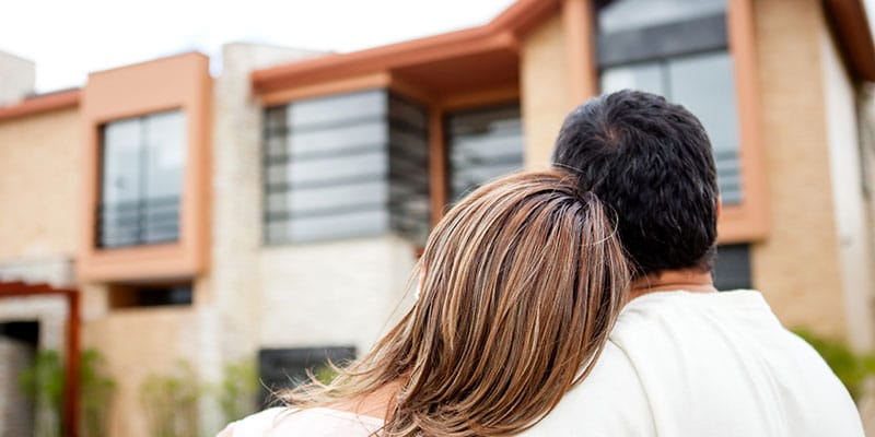 hugging couple looking up at their new home exterior