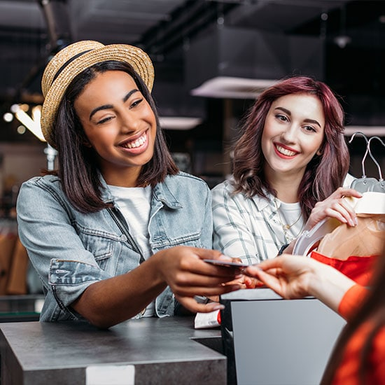 happy women out shopping together, handing card to cashier
