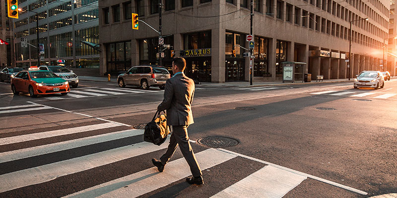 businessman walking across the crosswalk
