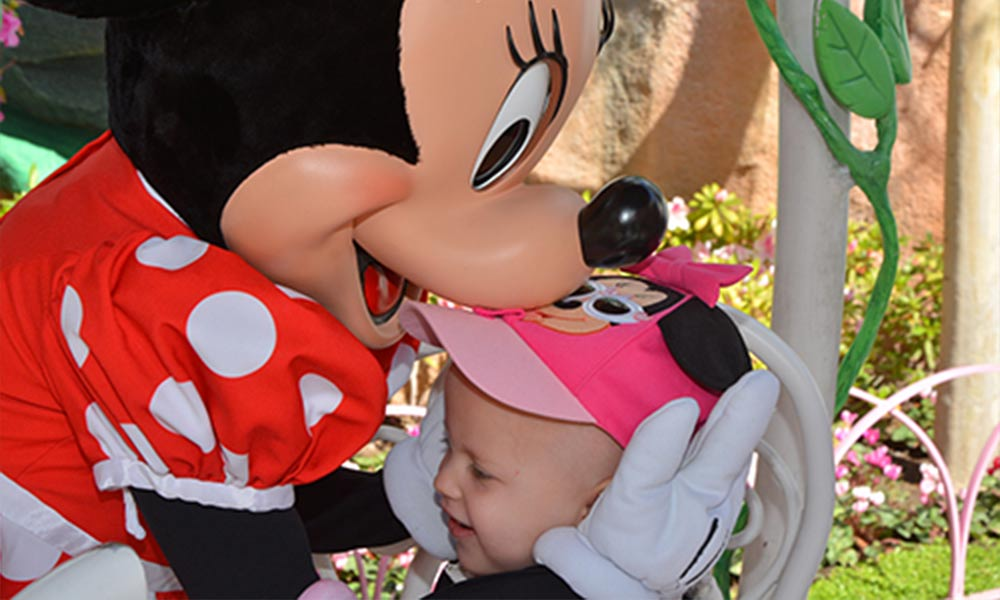 Minnie Mouse hugging little girl in pink hat