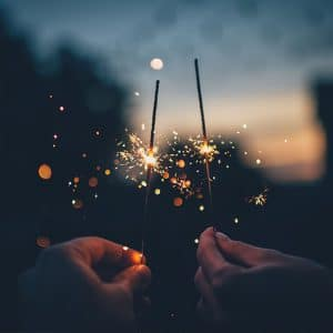 two people holding sparklers out at sundown, shallow depth of field