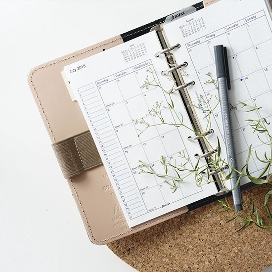 calendar planner open with a pen and floral sprig on top