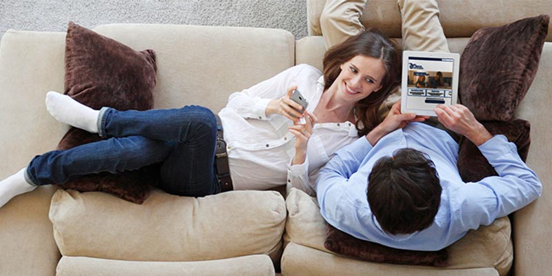 couple relaxing together on their couch with smartphone and tablet