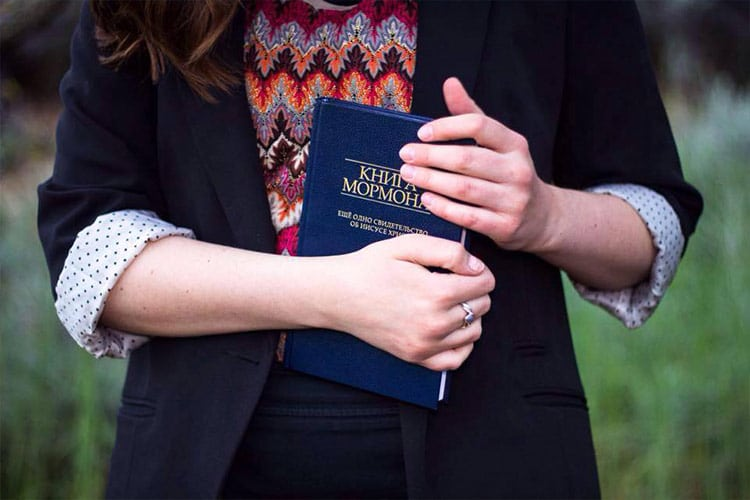 Sister missionary holding a copy of the Book of Mormon in a foreign language