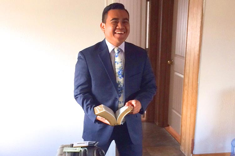 photo of a missionary in a suit, holding scriptures, standing next to his luggage