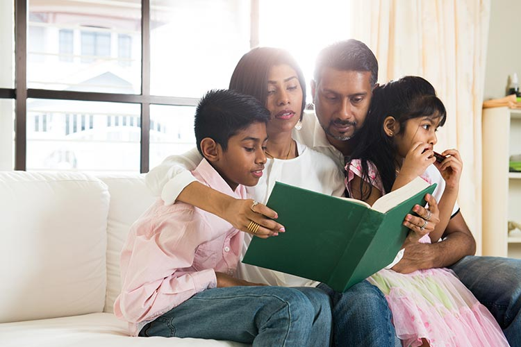 family reading a book together at home