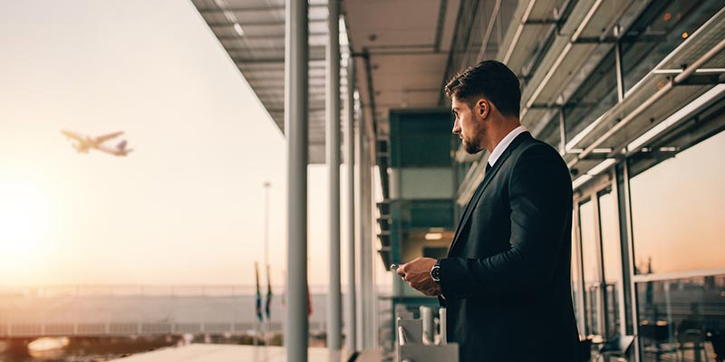 businessman in a suit at the airport, airplane flying away in the distance