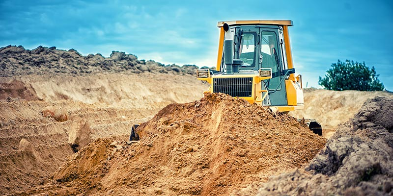 bulldozer pushing dirt in empty lot