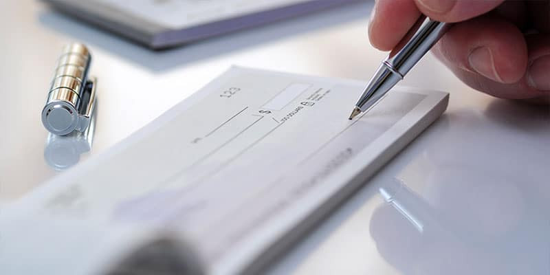 close up of hand signing a checkbook