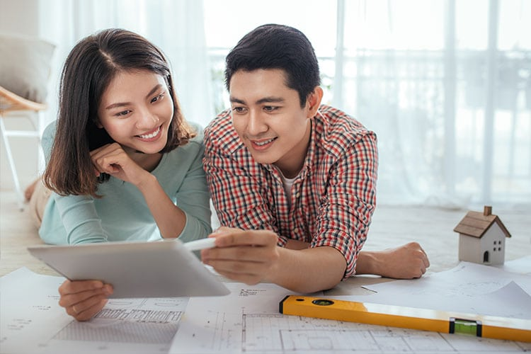 couple reviewing architectural plans for their new house