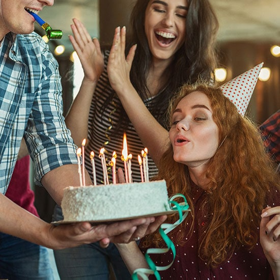 young adult friends celebrating a birthday together, blowing out candles on a cake
