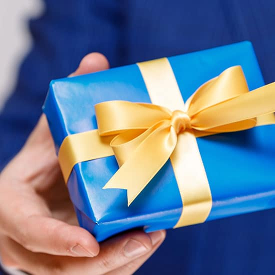 man holding a blue gift box with a gold ribbon