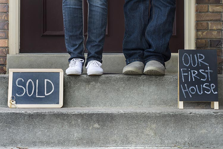 young couple on the steps of their first home with chalkboard signs reading 'sold' and 'our first house'