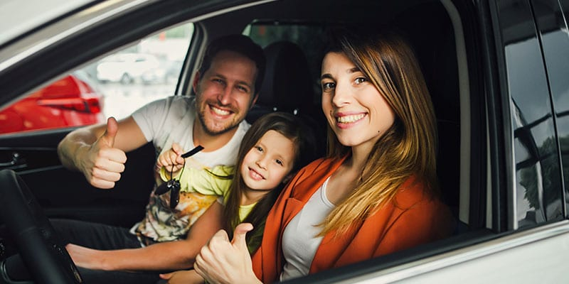 happy family sitting in their new car