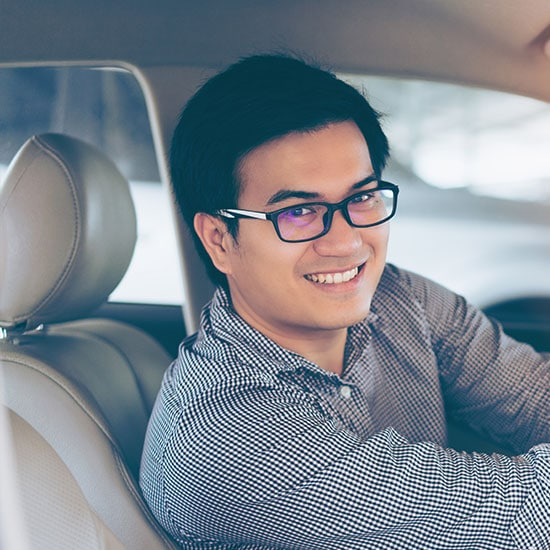 smiling man sitting in the driver seat of his car