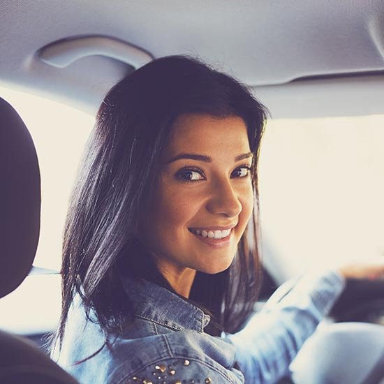 excited woman in the driver seat of her car, holding up the keys