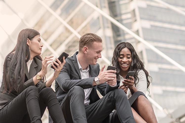 group of business professionals checking their phones and smiling together