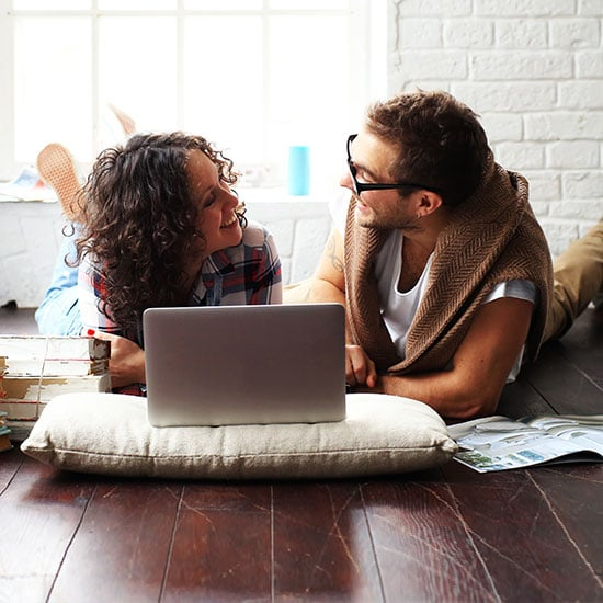 couple on the floor of their apartment looking at a laptop together