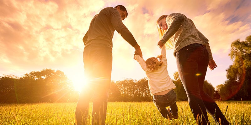 parents holding child's hands in an open field