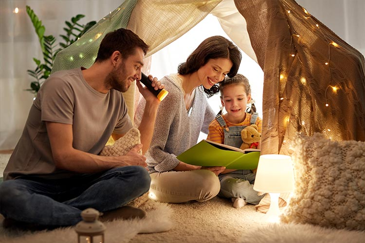 mother, father, and daughter inside a blanket fort reading a book together