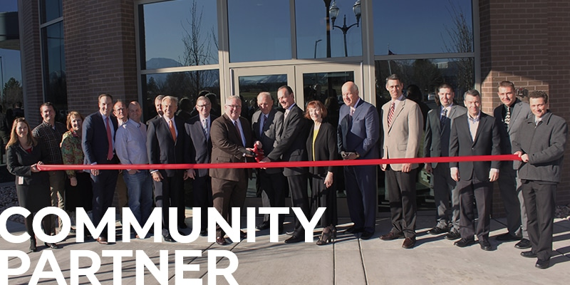 Deseret First staff along with members of the West Valley Community, DFCU's Board of Directors, and many others at the Ribbon cutting of the DFCU Operations Center, with a text overlay: Community Partner