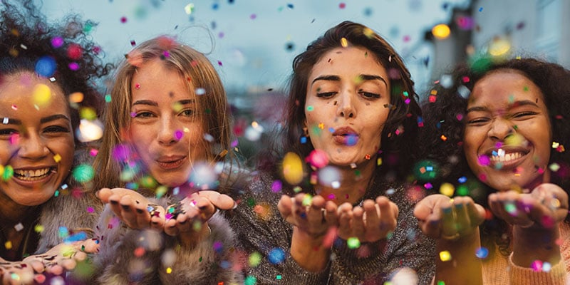 group of young women blowing confetti and laughing