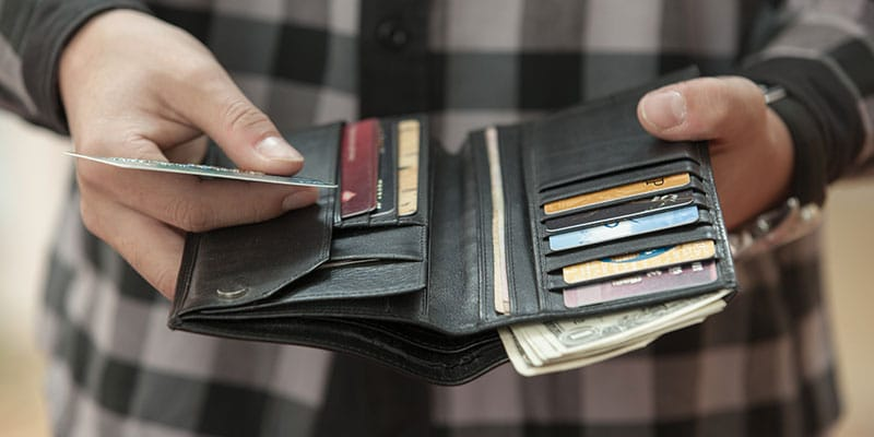 man holding his wallet out, credit card in hand