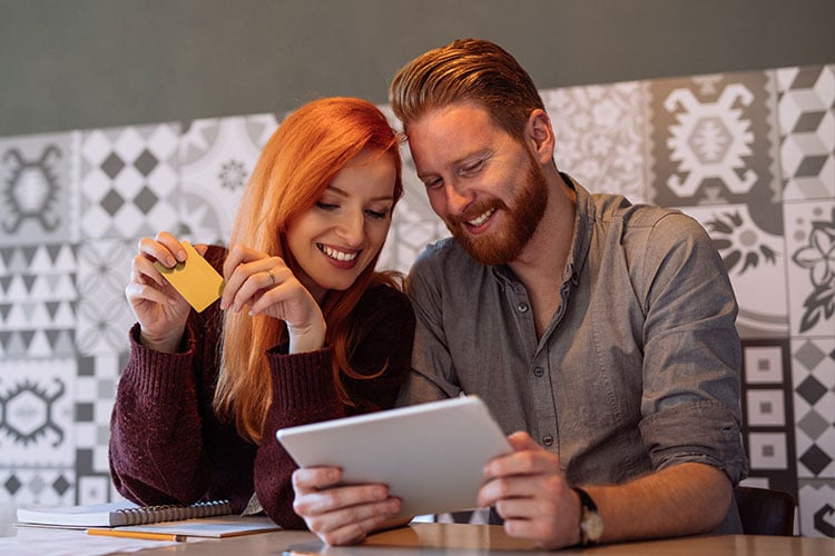 couple looking at a tablet, woman has a credit card in hand