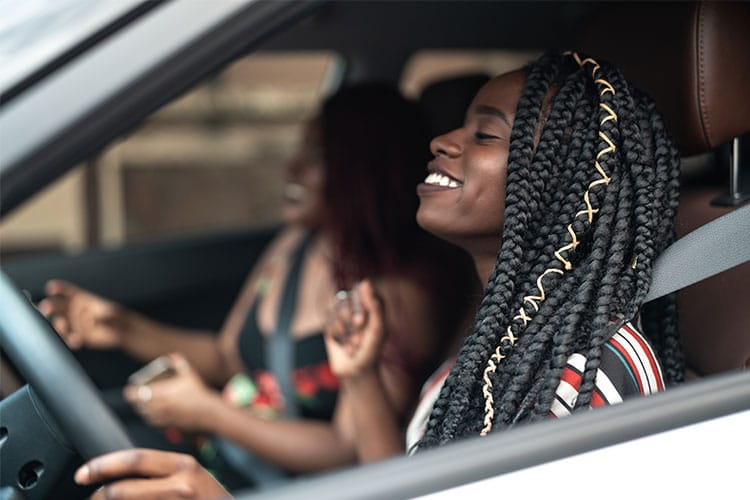two women smiling, jamming and driving in the car together