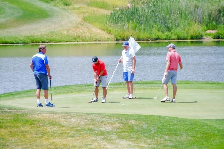 a group of four men playing golf