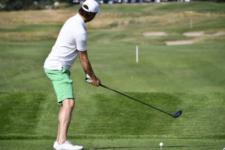 a male golfer preparing to swing the club on the green