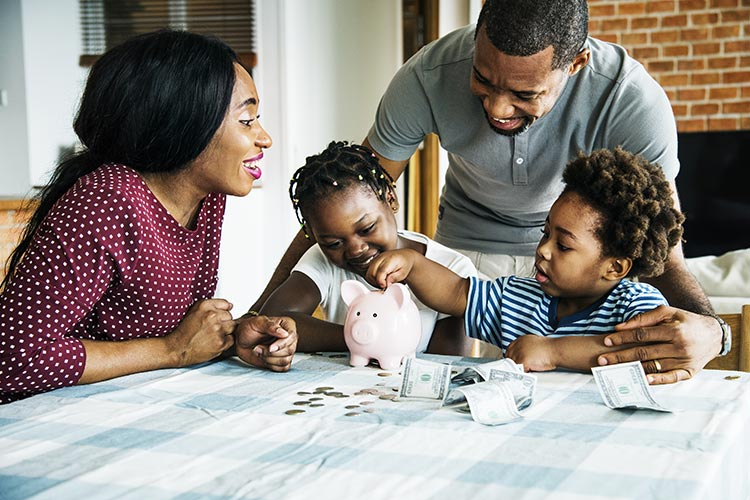family at the table together, counting their money into a piggy bank