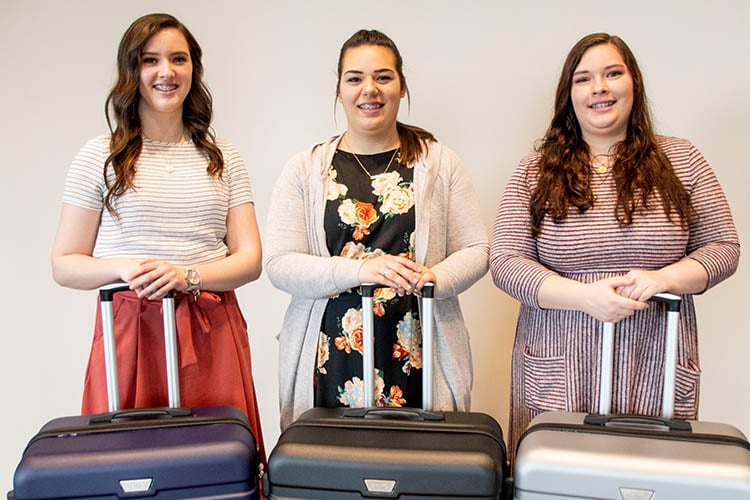 sister missionary triplets with their donated luggage